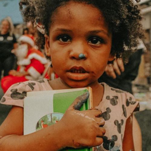 Menina recebe livros em ação da Bienal da Quebrada/Reprodução