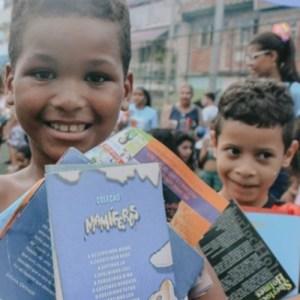 Em ação da Bienal da Quebrada, meninos recebem livros/Reprodução
