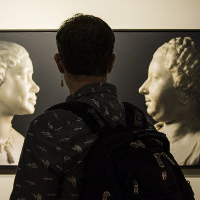 A student regards Gonzales-Day's 2011 photograph Untitled (Henry Weekes, Bust of an African Woman [based on a photographic image of Mary Seacole], 1859, and Jean-Baptiste Pigalle, Bust of Mm. Adélaïde Julie Mirleau de Neuville, neé Garnier d'Isle from the John Paul Getty Museum, Los Angeles).