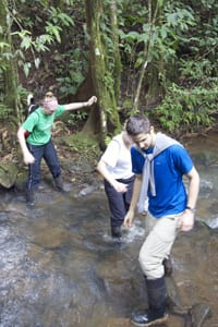 St. Olaf students (from left) Ellen Hawley '13, Justine Dammermann '14, and Andy Catania '13 navigate a river crossing in Costa Rica that they worked into their educational trail. As part of the project, the students engineered a stone bridge and carbon fiber hand rail to help trail users safely cross the river.