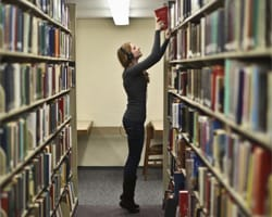 Samantha Botz '14 shelves books in Rolvaag Library. St. Olaf and Carleton colleges have already merged their library collections into the Bridge, and materials are exchanged between campuses via a twice-daily courier. Photo by Star Tribune photographer Renee Jones Schneider '01