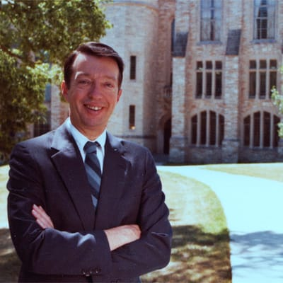 Former St. Olaf President Mel George poses in front of Holland Hall on the St. Olaf campus.