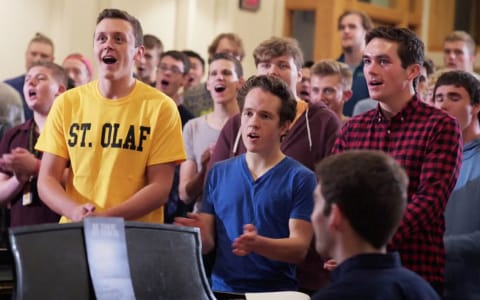 "Levi Wick '19 (in the St. Olaf shirt) participates in a choir rehearsal on campus. He says being a member of a St. Olaf choral ensemble provides ""a sense of community, the chance to sing with amazingly talented and dedicated individuals, and the opportunity to touch people's hearts through music."""