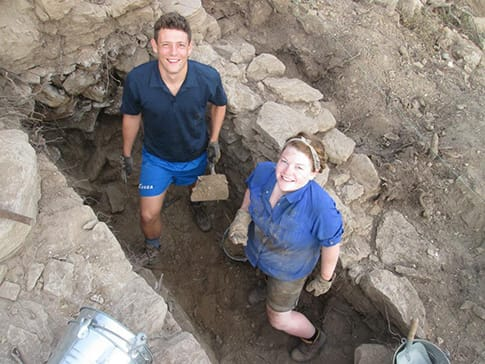 Two students working in an excavation trench at a dig site