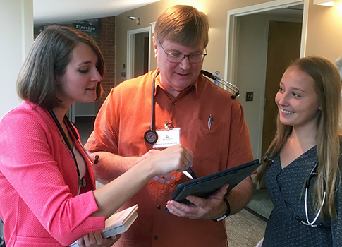 St. Olaf College students Taylor Knopf '18 (left) and Morgan Turk '18 (right) speak with Chris Johnson '76.