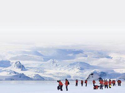 Women scientists walk on a glacier.