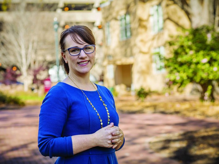 Woman with glasses standing in sunny courtyard