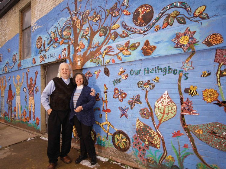 Patrick and his wife standing in front of a mural.