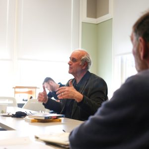 Man sitting at a table speaking to a group.
