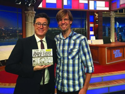 Stephen Colbert holding a book next to Ward Sutton.