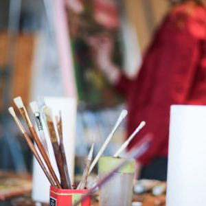 Paint brushes in a cup with woman painting in background