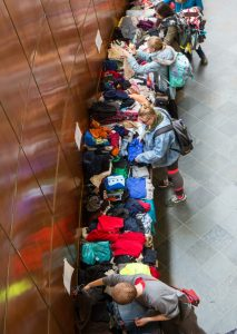 Students looking through clothes on a long table.