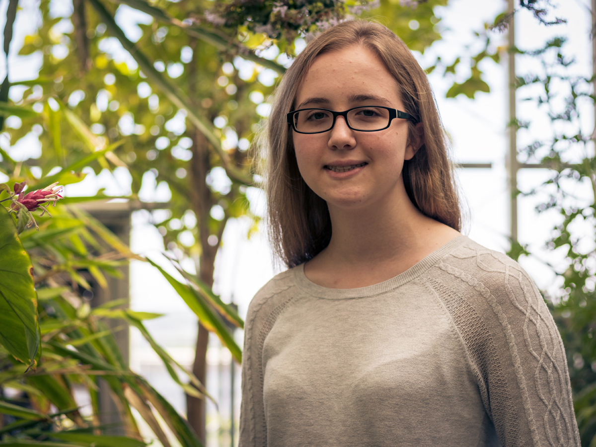 Catherine Gilbert stands in front of plants in the St. Olaf greenhouse.