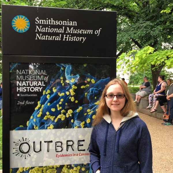 Catherine Gilbert stands in front of a Smithsonian National Museum of Natural History sign.
