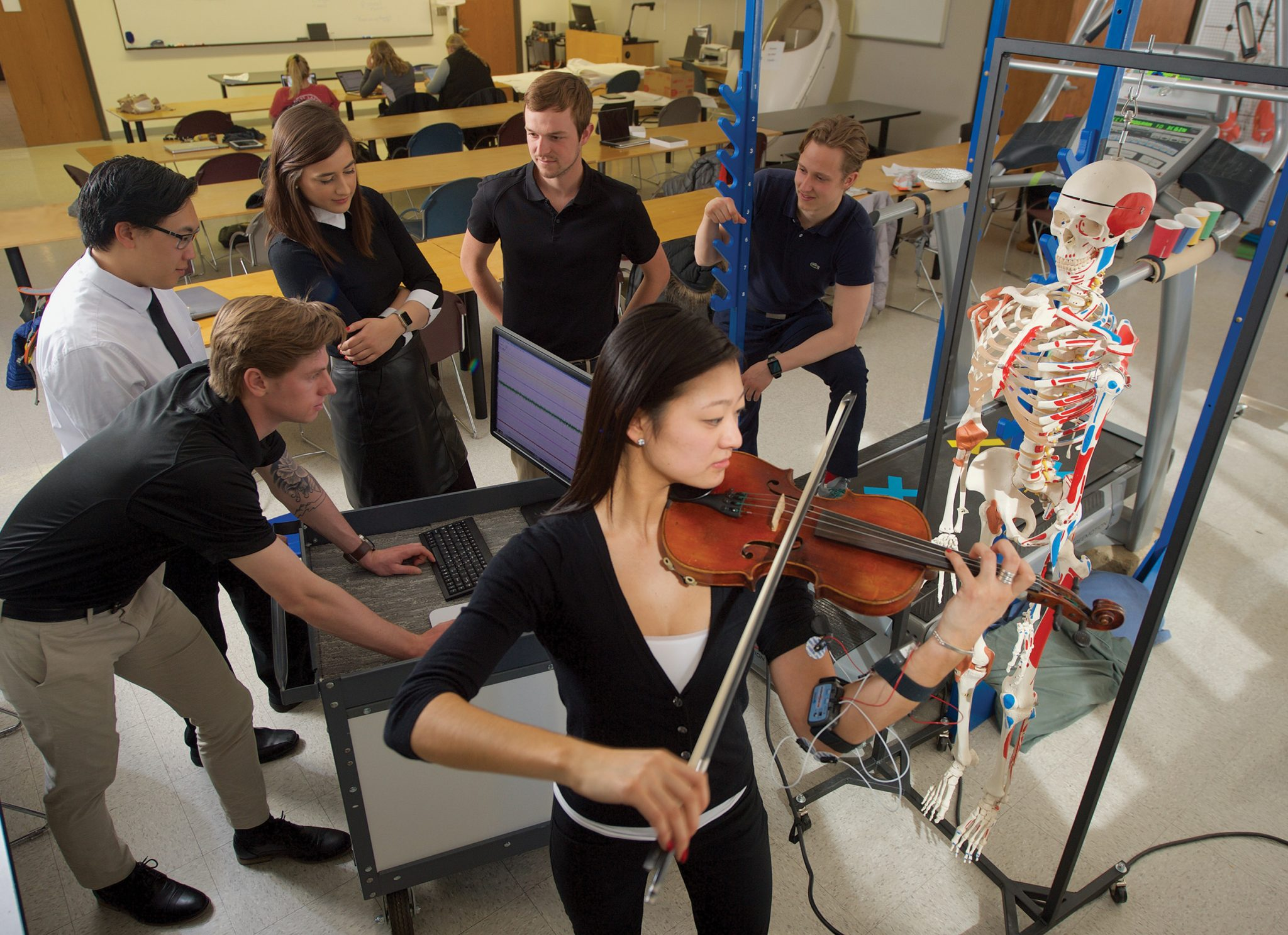 Woman playing violin in front of students looking at a computer monitor.