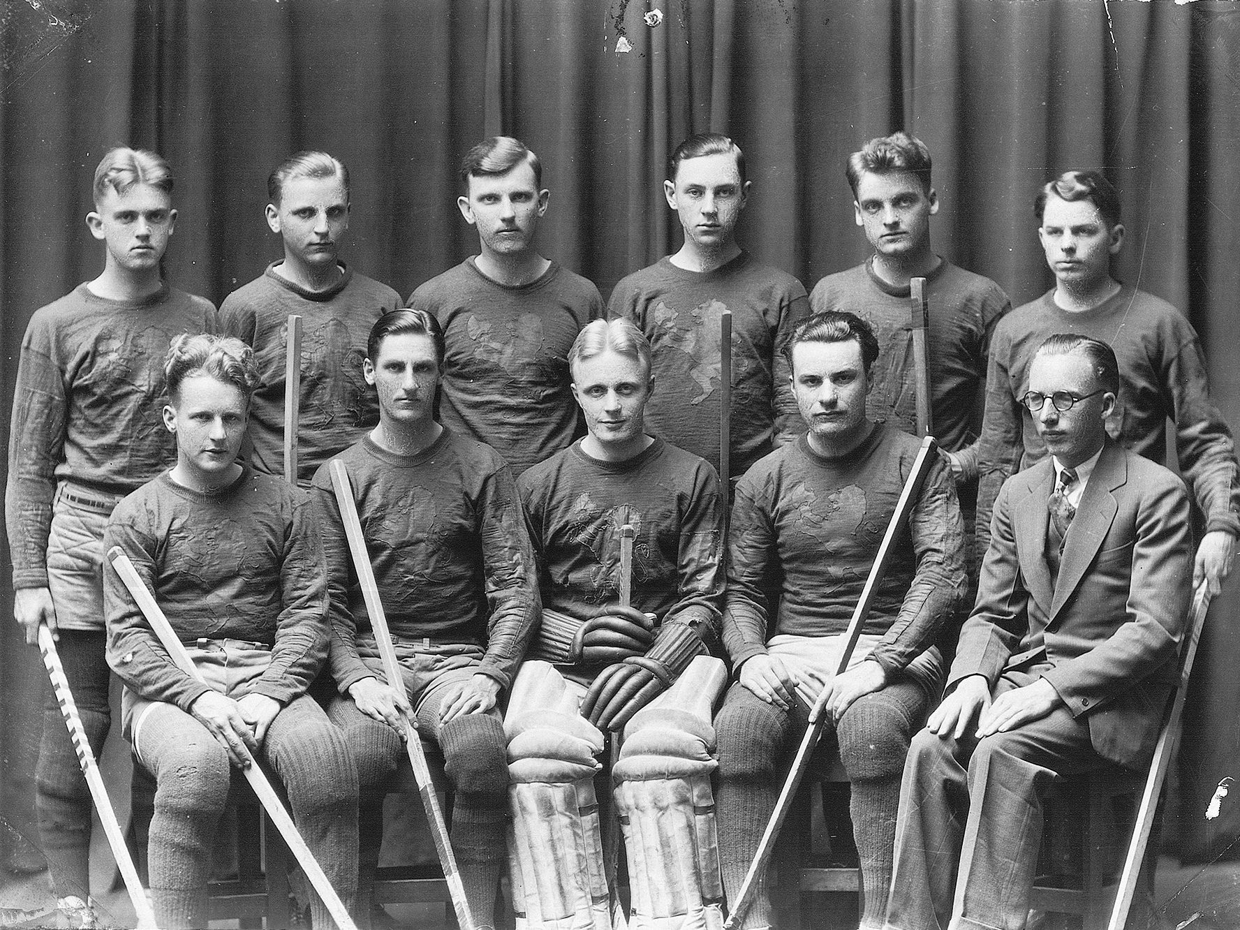 Group photo of original Ole Pucksters in uniform with hockey sticks