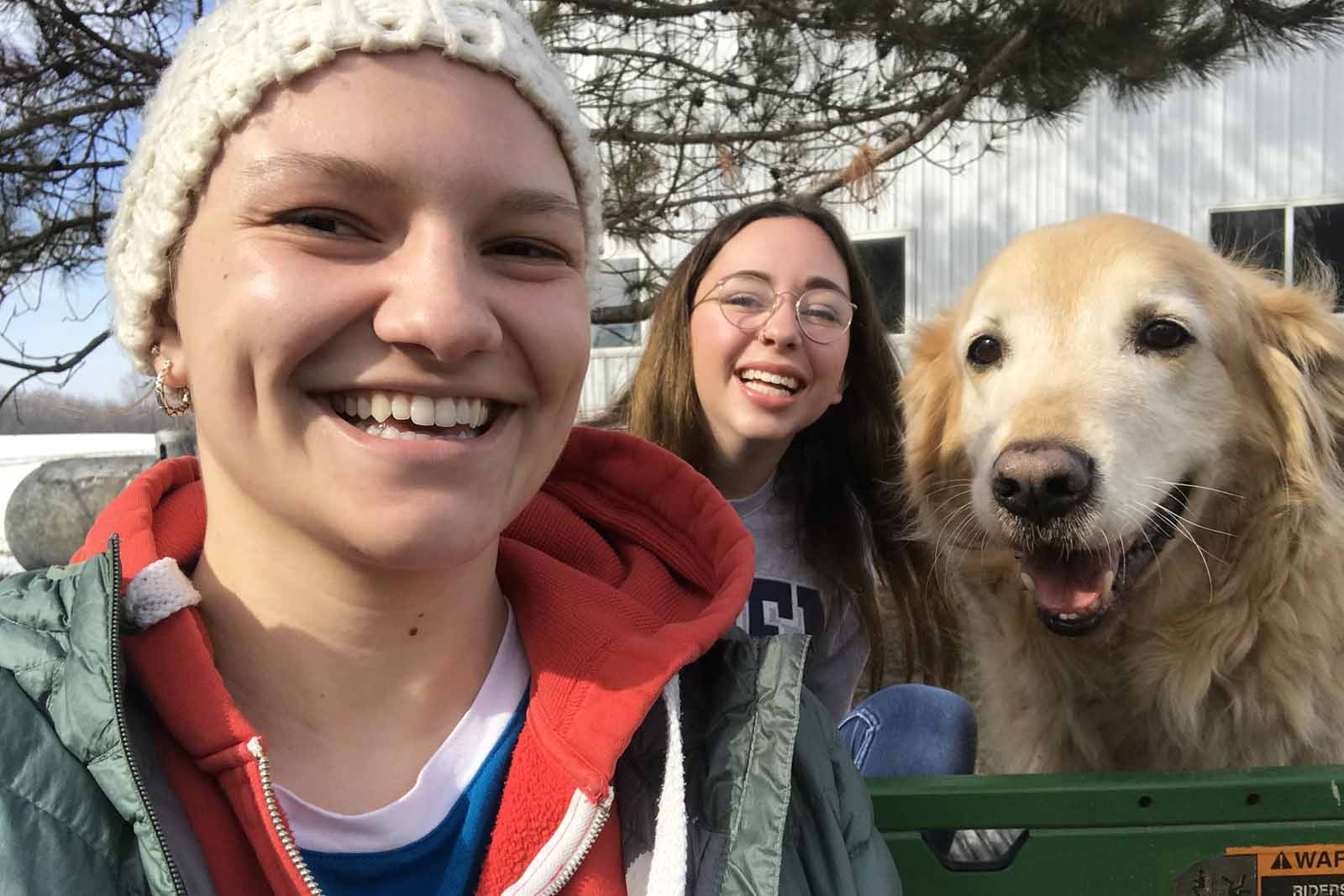 Greta Van Loon '22 (front) and her American Conversations group mate Marlee Baron '22 take a tour of Dave Legvold's farm while visiting to interview him for their podcast.