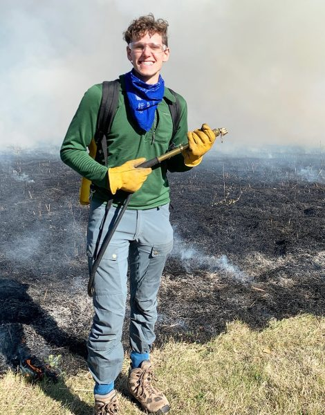 Portrait of student naturalist Henry Henson doing a controlled prairie burn.