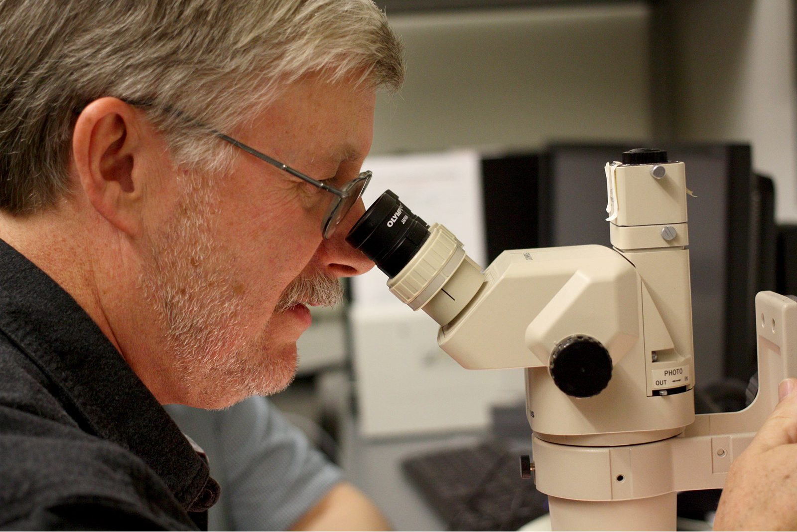 Professor of Biology Eric Cole looks through a microscope at a laboratory slide. Last spring, Cole devised a way to share live microscopy images and conduct research directed by his students while they learned from home.