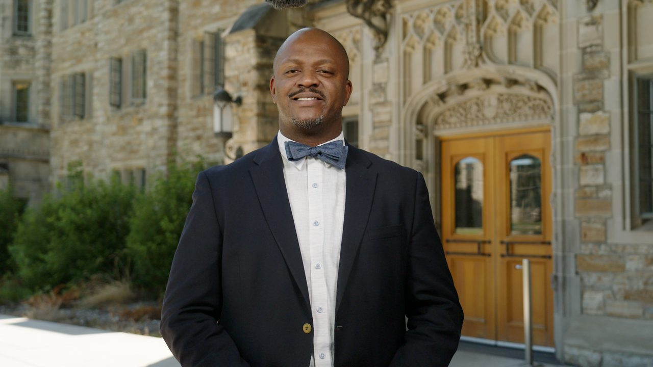 A portrait of Vice President for Student Life Hassel Morrison in front of Mellby Hall