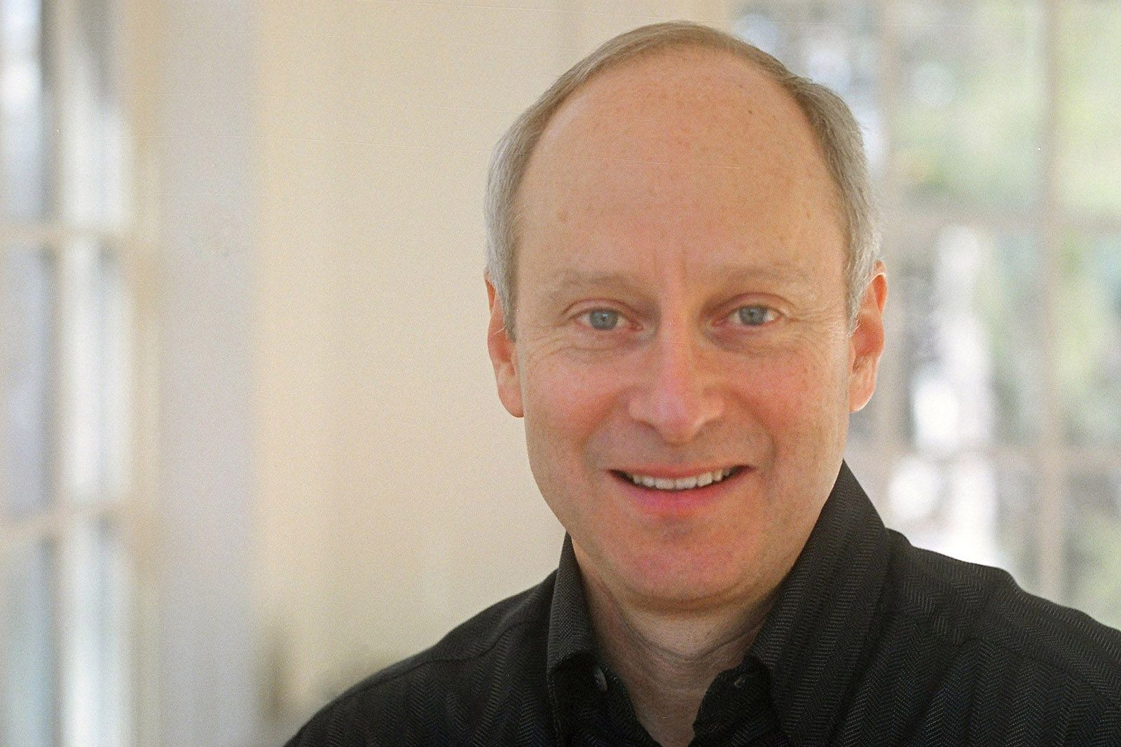 A portrait of Michael Sandel wearing a black shirt, with two windows in the background.