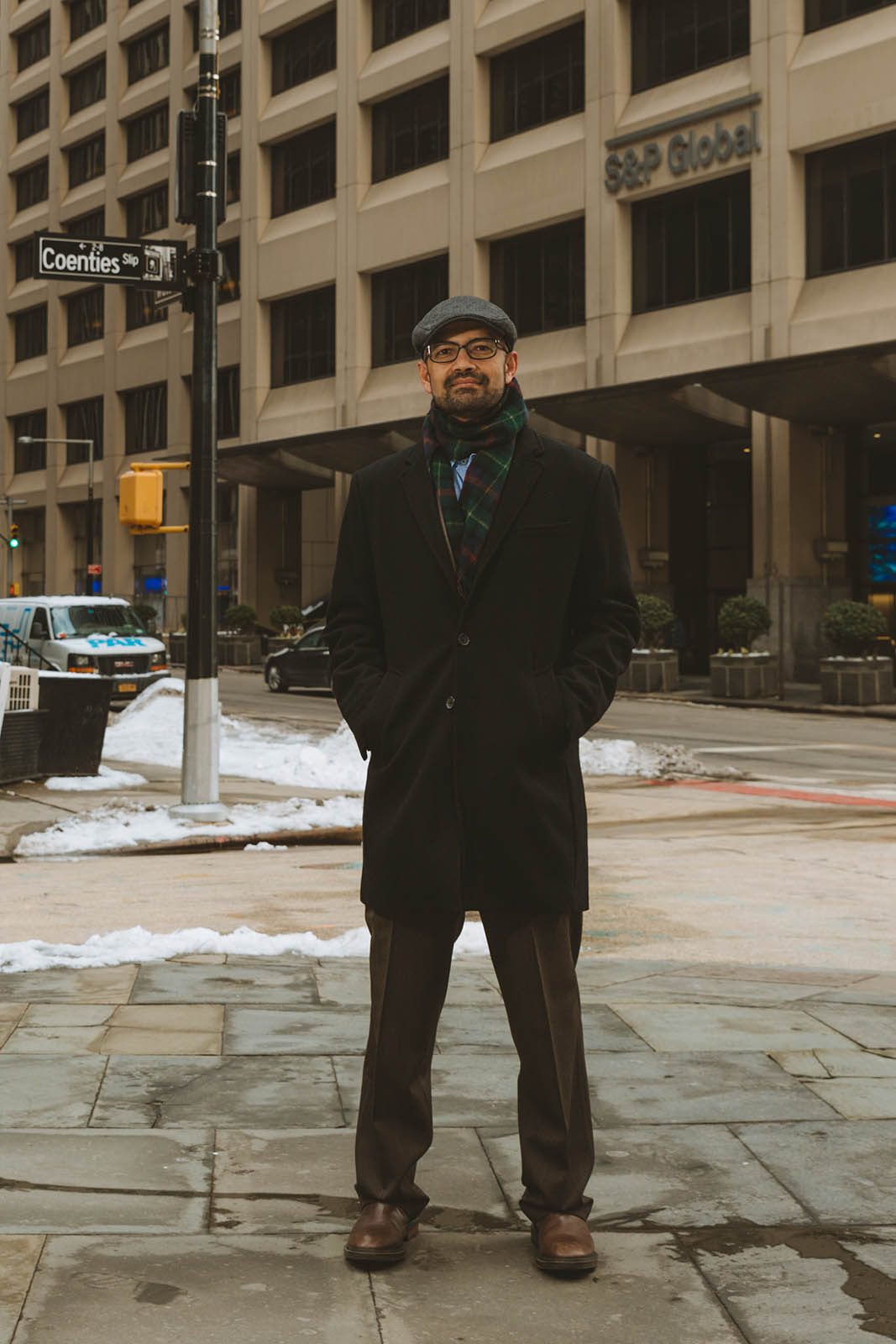 Portrait of Satyam Panday on a New York city block with a brown building in the background.