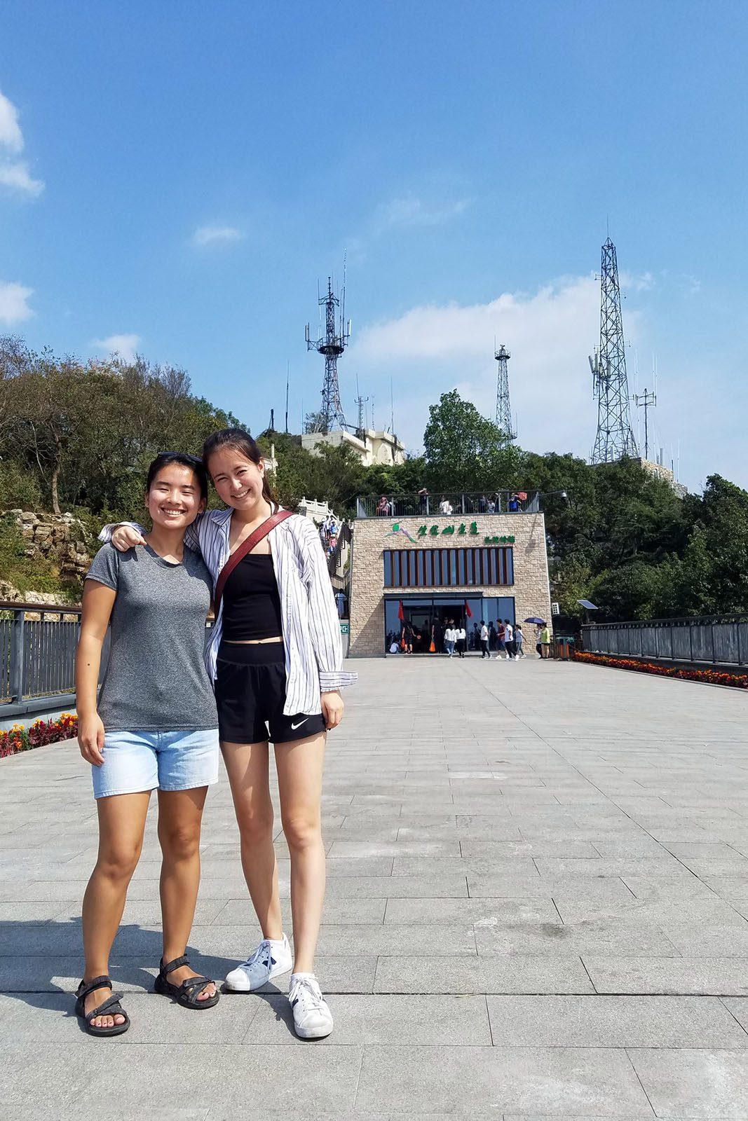 一つアンダーソン(右)と友達に建物、木、基地局、青空を背景に石橋の上に立っている。