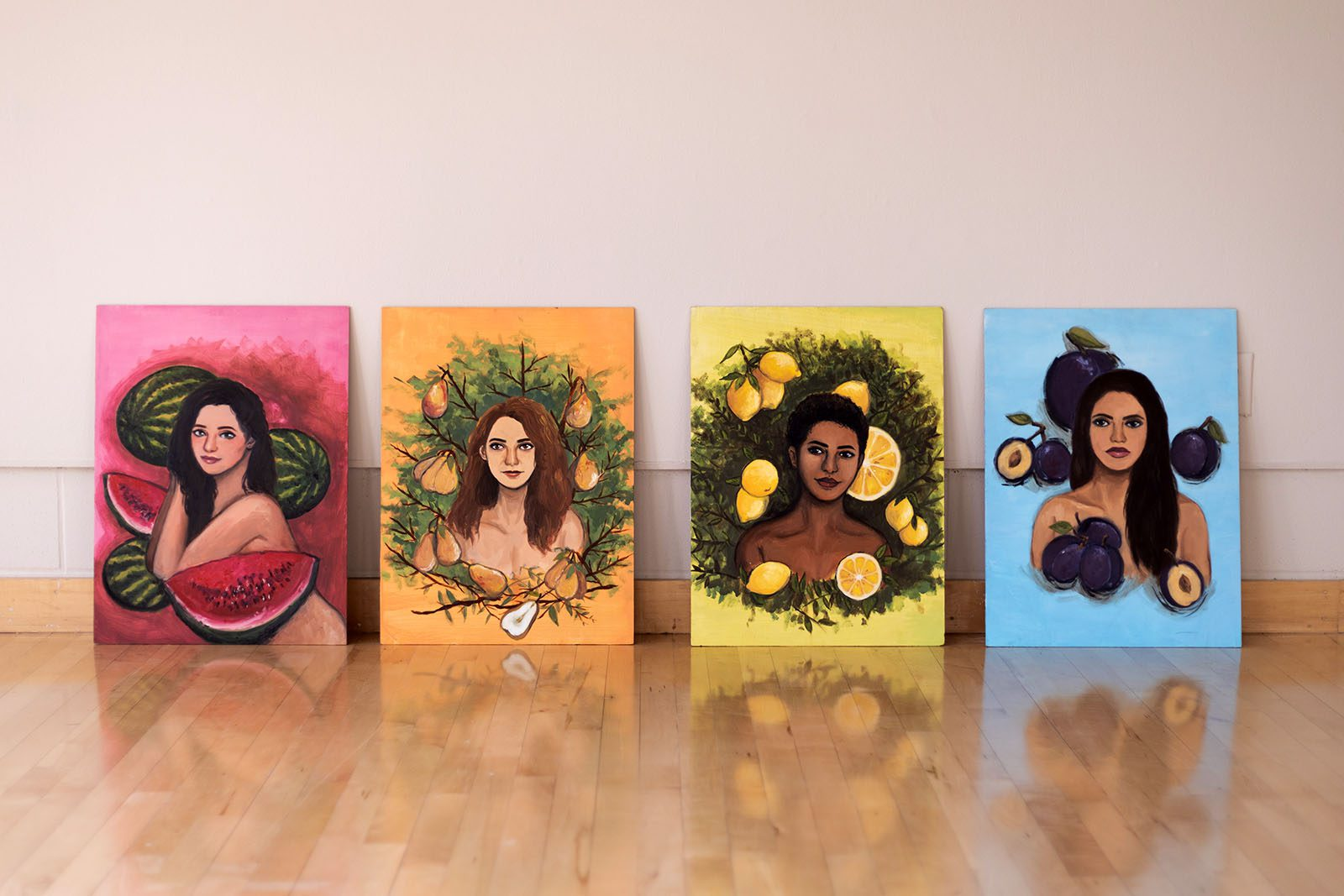 A photo of four paintings, each featuring a portrait of a woman surrounded by fruit. The paintings rest on a hard-wood floor and against a white wall.