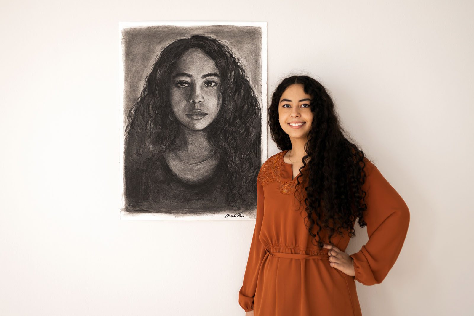 Portrait of Amanda Rose next to a black-and-white self-portrait in front of a white wall.