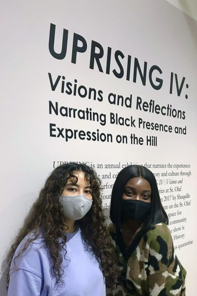 Picture of Amanda Rose and Bridget Asamoah-Baffour in front of a wall in the UPRISING exhibit.