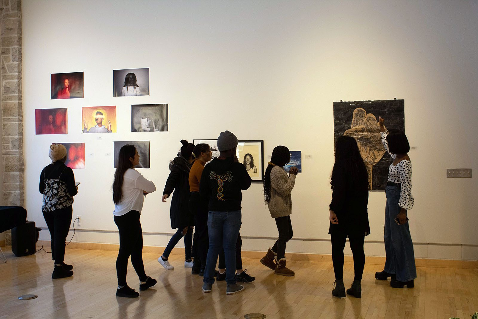 Students walk around a gallery with art on the white walls.