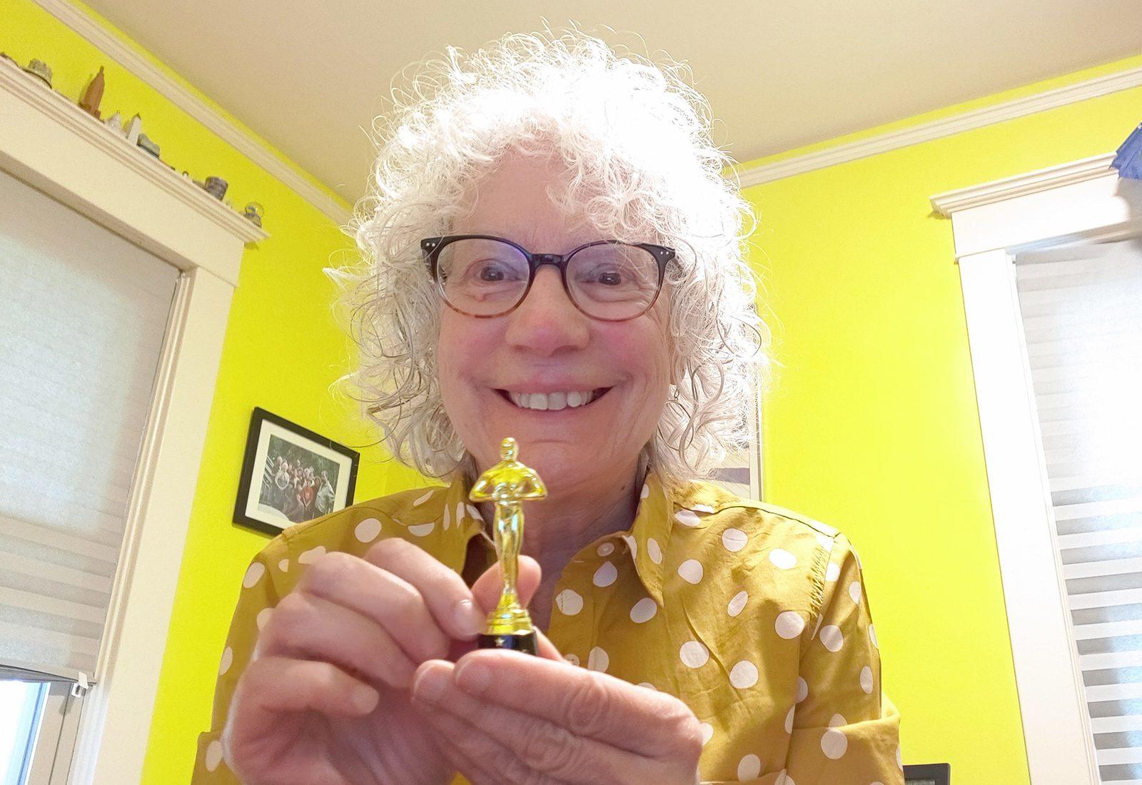 Professor of History Judy Kutulas holds a miniature Oscar.