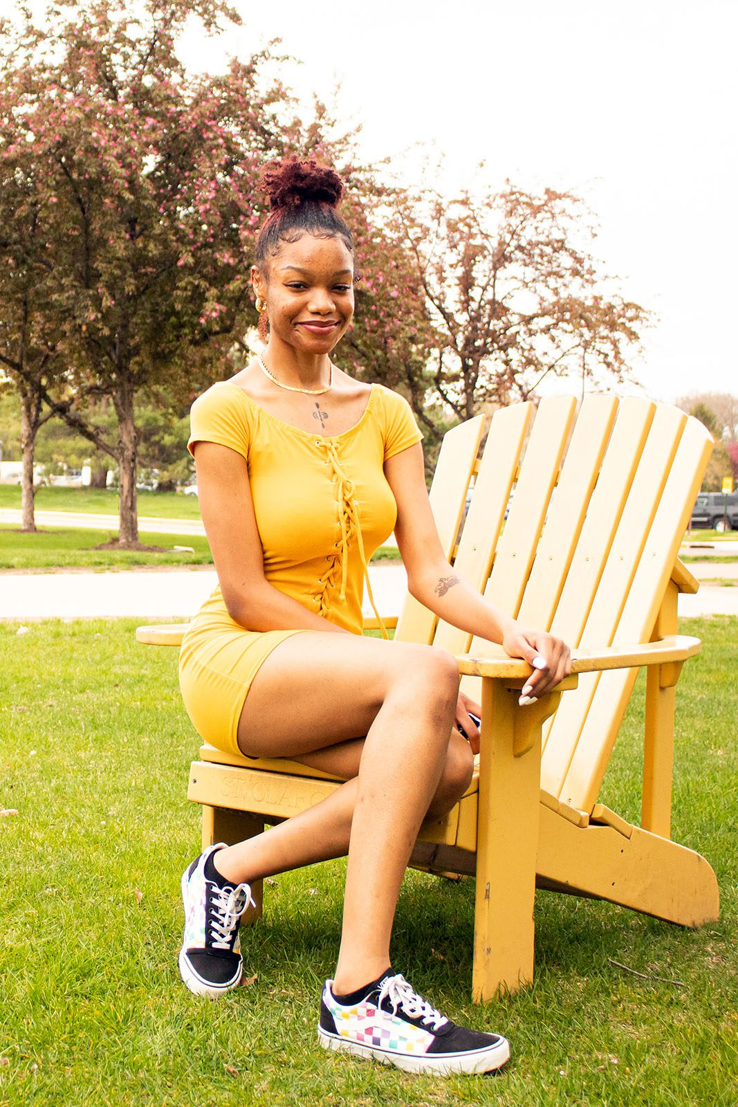 Portrait of Tija Atkins on a yellow adirondack chair with trees in the background.