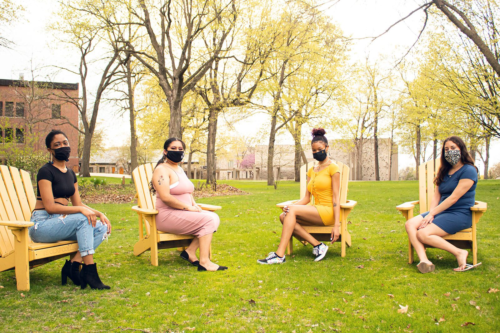 Portrait of (from left to right) Sophia Evans, Joanna Perez, Tija Atkins, and Allyvia Garza on adirondack chairs in the grass with a red brick building, a limestone building, and trees in the background.