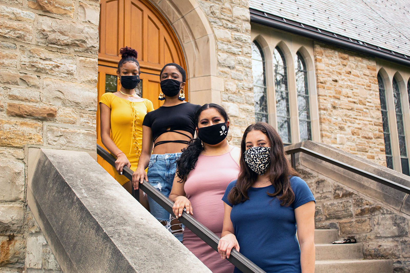 Portrait of (from left to right) Tija Atkins, Sophia Evans, Joanna Perez, and Allyvia Garza on a stone staircase with a stone building and wooden door in the background.