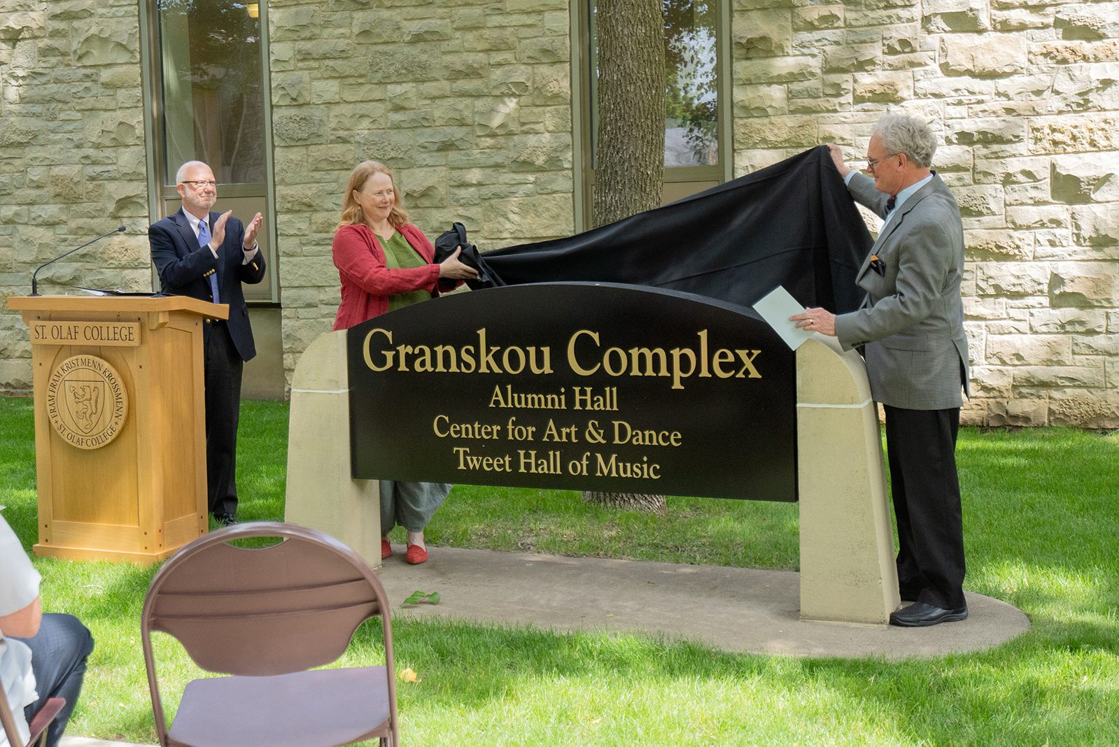 President David R. Anderson '74, Professor of Music and Music Department Chair Kathryn Ananda-Owens, and Associate Provost and Professor of Music and King Olav V Chair in Scandinavian-American Studies Dan Dressen unveil the new sign recognizing Tweet Hall of Music as part of the Granskou Complex.