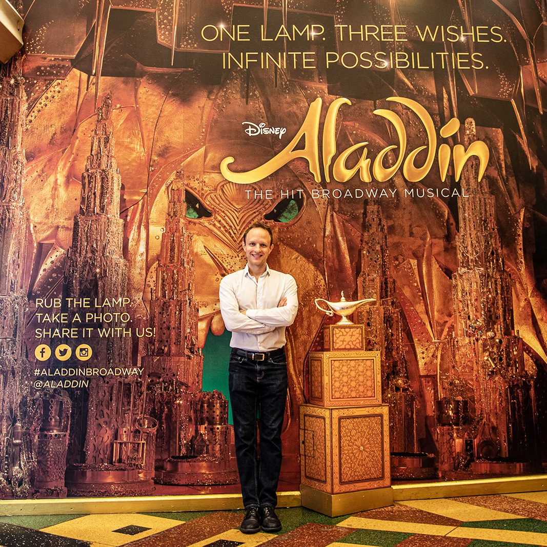 """Aron Accurso '01 in front of an advertisement for the hit Broadway musical """"Aladdin,"""" which has earned five Tony nominations, including Best Musical."""