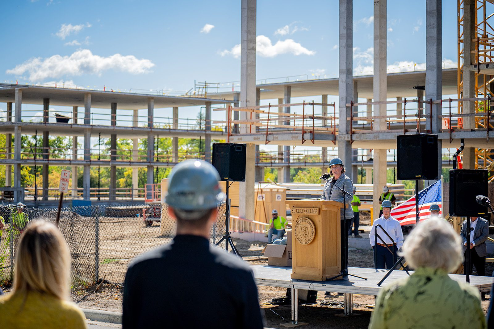 Associate Dean of Students for Residence Life Pamela McDowell speaks at the topping out ceremony, with the Ole Avenue Project construction behind her.