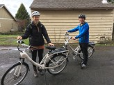 Woman and man in 20s each pose with Solexity ebike in street