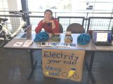 Man in 20s runs eBike booth in Viking Union and smiles for camera