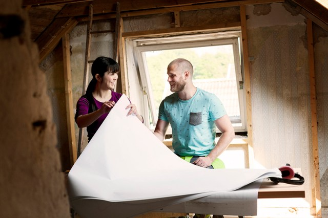 Couple looking at renovation plans while remodeling a home.