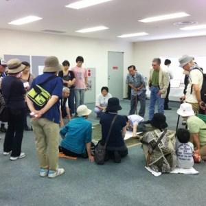 画像:絵を描く佐藤さんとそれを見守る来場者の方々