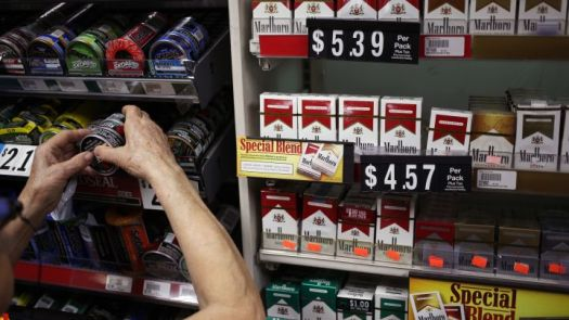 An employee stocks cans of tobacco beside a display of Marlboro brand cigarettes inside a tobacco store in Nashville, TN.