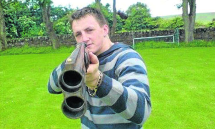Dennis Cox with a gun