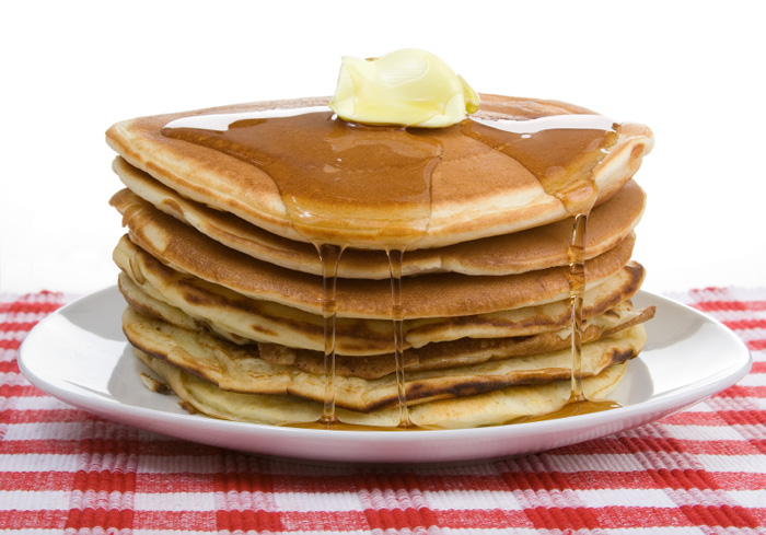 A stack of pancakes with a pat of butter on top, sitting on a white plate and a red and white tablecloth.