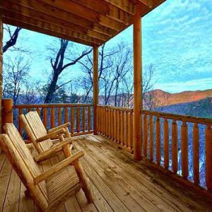 Rocking chairs on a deck overlooking a mountain winter sunset