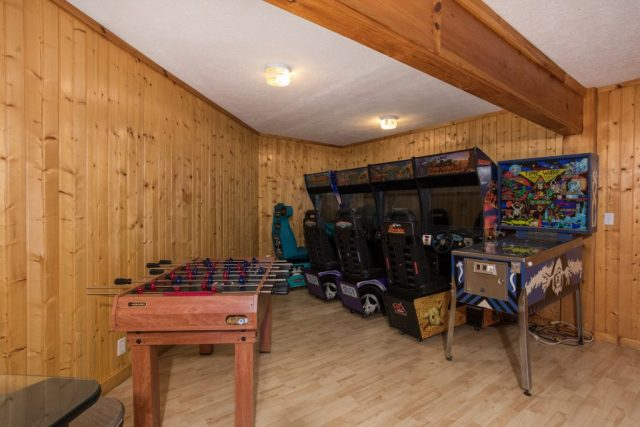 Game room with driving games and pinball at Breezy Mountain Lodge. A Pigeon Forge rental cabin.