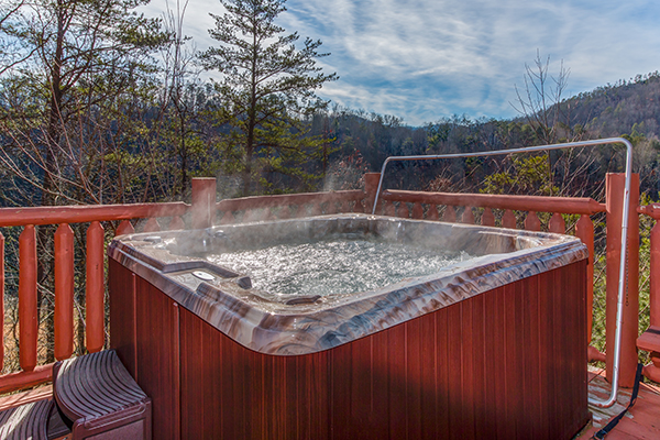 A steamy hot tub on a deck overlooking the Smoky Mountains