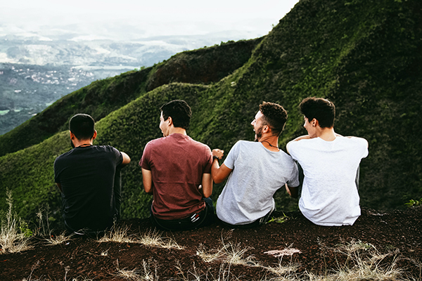 four men laughing on a mountain peak