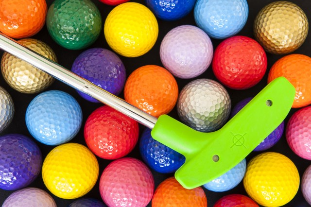 multicolored golf balls and a putter